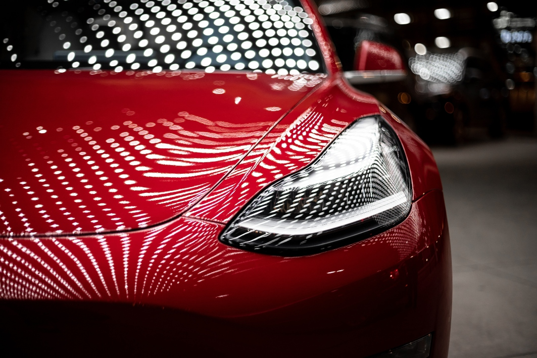 close-up-of-front-of-red-tesla-in-parking-gara
