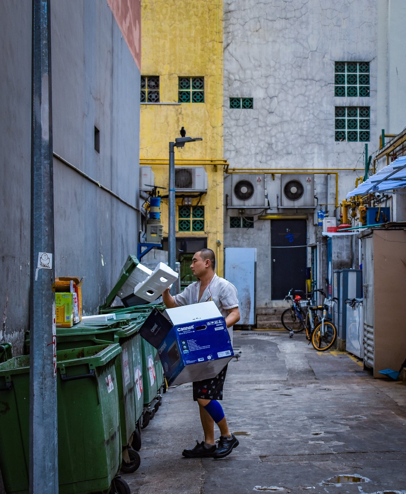 man-taking-out-trash-in-alley