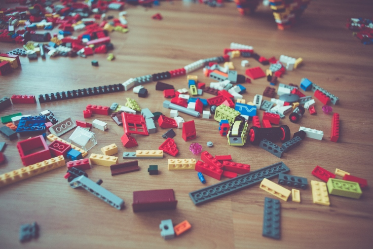legos-scattered-on-wooden-floor