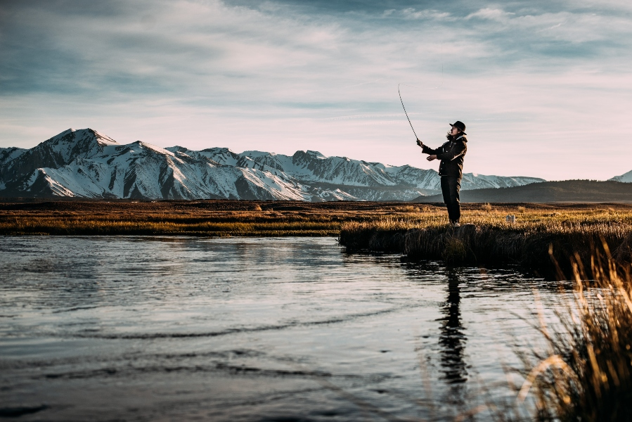 man-fly-fishing-mountains-in-background