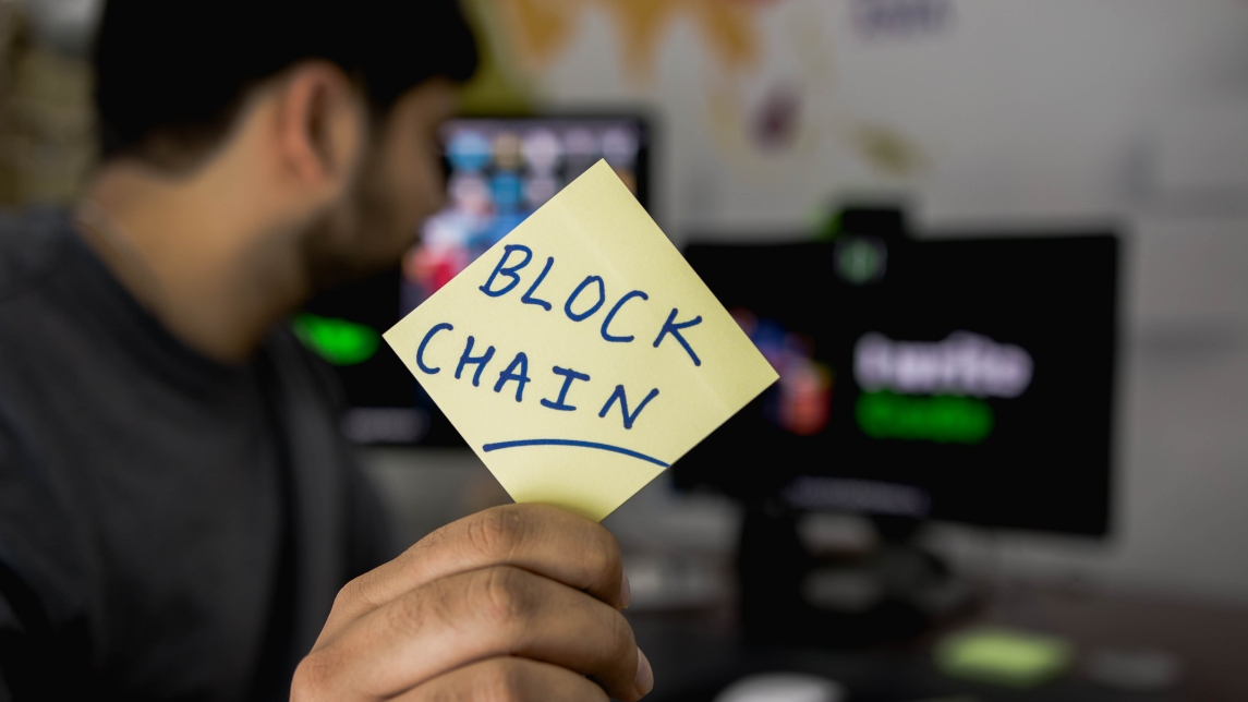 man-holding-sticky-note-blockchain