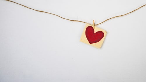 A drawing of a little red heart hanging on a brown string on a white wall