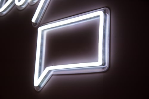 White glowing square message bubble mounted to a wall