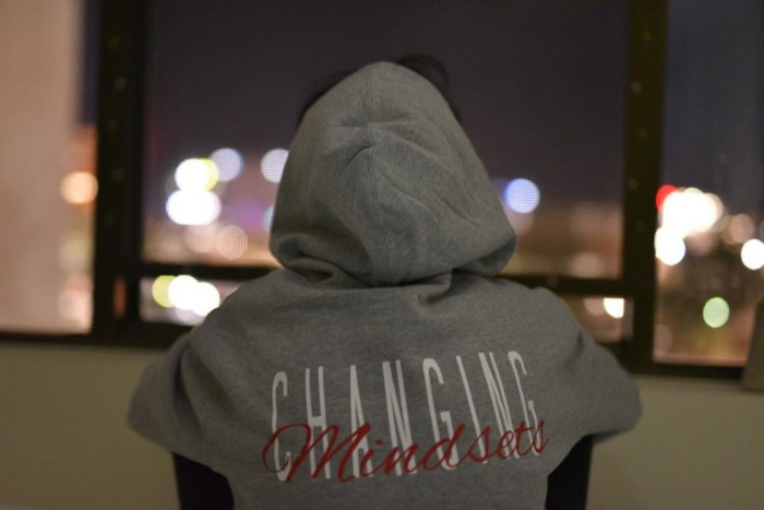 "person wear hoodie that reads ""changing mindset"""