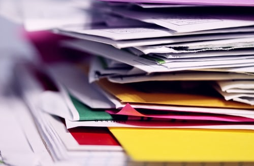 Files stacked messily on a desk