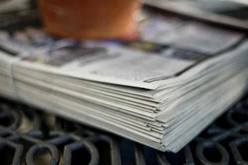 stack of newspapers on metal table